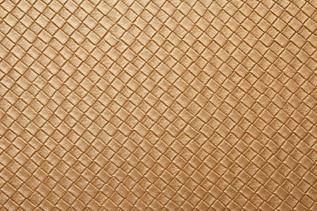 golden leather texture on sofa or brown fabric and blank wood wall or top view empty table with grid and diamond or square pattern for background or wallpaper