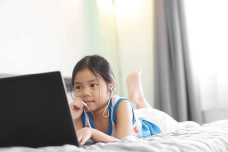 Asian child student or kid girl wear earphone or headphones and small talk to study online or work from home on computer notebook or play laptop communication on bed by education school and stay safe Stockfoto