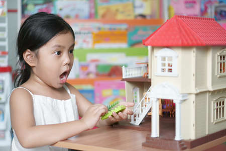 Asian child cute or kid girl thinking playing toy for learning education on build a house or family home and finance investment or future money development with real estate at nursery school and wow Stockfoto