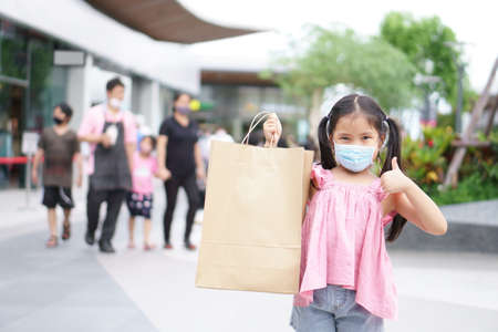 Asian child or kid girl smile wear face mask and holding empty recycle paper bag to enjoy shopping and fun with thumb up for like and good at department store or market mall to family
