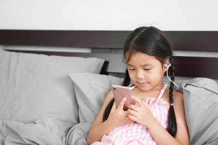 Asian child or kid girl smile wear headphones or small talk to learn study online or work from home on smartphone and mobile phone communication or people listen music and leaning relax pillow on bed