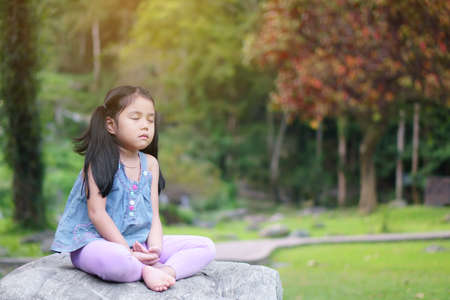Asian child cute or kid girl close eye mindfulness meditating with breath and sit on stone or rock for peace and yoga relax on nature green garden and red tree at temple park and outdoor warm sunlight Stockfoto