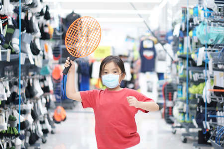 Asian child exercise or kid girl wear face mask with holding small tennis racket or plastic squash and badminton with arms raised for hit ball on sport mall shopping in department store to healthy