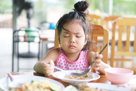 Asian child cute or kid girl anorexia or sad and bored food or boredom with frown on wood table for breakfast or lunch eating at restaurant on preschool or nursery