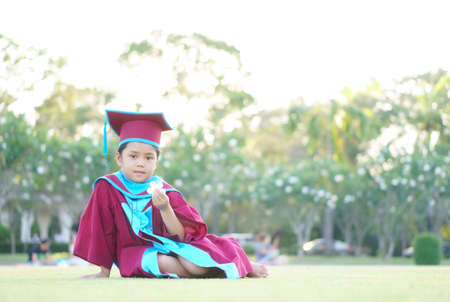 Asian child or kid girl smile and little graduate wear gown and degree hat on nature green grass by kindergarten success to primary education school and holding white plumeria flower to congratulation