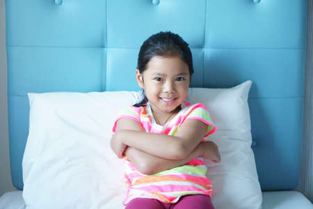 Asian child cute relax or kid girl sleep and wake up with fold arms and smiling good mood for refreshing or sweet dream in morning on blue bed and white pillow in bedroom at home or hotel on holiday Stockfoto