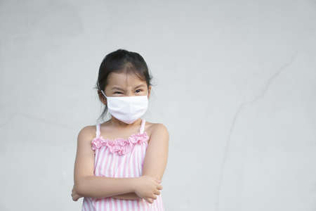 Asian child angry or kid girl frown wear cloth face mask for close mouth nose and cold cough sick to protect influenza covid-19 or coronavirus and PM 2.5 dust with bacteria by smoke and crossed arms
