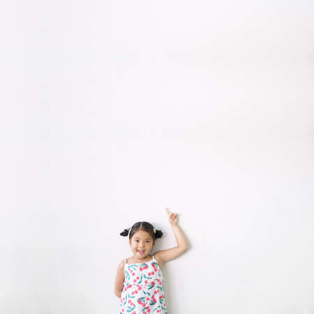 Asian child cute or kid girl thinking smiling with finger point on top for new idea and imagination or creativity education with happy at nursery preschool on white wall background and space isolated Stockfoto