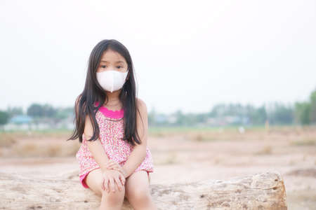 Asian child think new idea or kid girl wear N95 face mask and flu sick with cold cough sneeze for protect covid-19 virus or PM 2.5 dust by smoke or air pollution and close mouth nose to unhappy sad Stockfoto