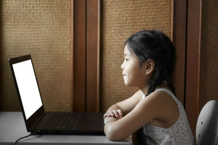 Asian child student or kid girl study online or work from home on computer notebook or play laptop and watch or look to empty display on desk by education school with clipping path for white monitor Stockfoto