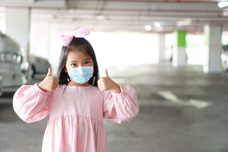 Asian child or kid girl smile wear N95 blue face mask for close mouth nose and sick with flu cough and protect PM2.5 dust or coronavirus and smoke bacteria to thumb up for like on pink dress with bow