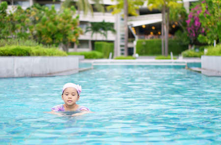 Asian child cute or kid girl wear swimming suit and cap on swimming pool and enjoy smiling with happy fun in water park for learn and training or refreshing and relax with exercise on summer holiday