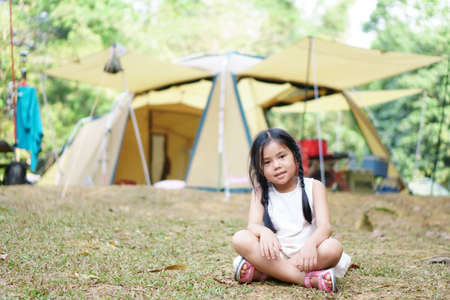 Asian child cute or kid girl camper sit on grass lawn and nature camping tent or cabin camp and happy smile in green forest for adventure holiday relax and family vacation travel at national park