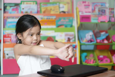 Asian child or kid girl study online or work from home on computer notebook or play laptop by pre elementary school education and ache to rest with stretch oneself smiling from covid-19 virus scourge
