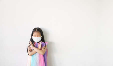 Asian child cross arm or kid girl strong wear N95 cloth face mask for close mouth nose and fight sick with flu cough and protect PM 2.5 dust or influenza covid19 corona virus on white space background Stockfoto