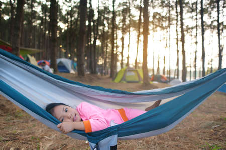Asian child cute or kid girl sleeping on hammock and happy smiling on nature green tree and pine jungle or forest for summer holiday relax or camping tent picnic and travel trip on family vacation