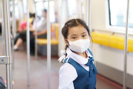 Asian child student or kid girl smile wear face mask in sky train or electric train with underground railways and metro subway to standing hold pole or rail in street city for back to school transport