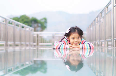 Asian child cute or kid girl happy smiling and sleep or lie down on skywalk with reflection and clear glass floor on mountain for vacation travel and holiday relax at khao laem in vajiralongkorn dam