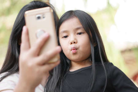 Asian child cute or kid girl and daughter selfie or taking photo together with mother or parent by phone or smartphone and happy shorten mouth or pucker up and kiss on family holiday vacation to relax