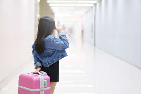 Asian child cute or kid girl dragging luggage or baggage and pink suitcase with wear sunglasses and denim shirt or blue jeans on walkway in airport for holiday travel relax and summer vacation trip Stockfoto