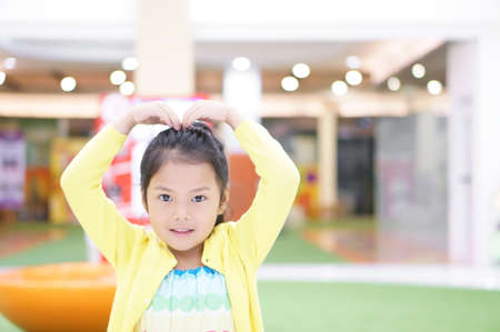 Asian child cute or kid girl lovely smiling and make heart by arm and hand on top head or Sarang-hae-yo for love valentine day or wedding with happy and enjoy with wear colorful dress and cheerful