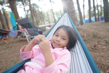 Asian child cute or kid girl sleeping relax on hammock and happy smiling on nature green tree and pine jungle or forest for holiday relaxation or camping tent picnic and travel trip on family vacation Stockfoto
