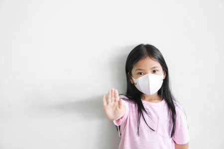 Asian child or kid girl wear N95 paper face mask 3D for close mouth nose and sick with cold cough and protect influenza virus or PM2.5 dust with hand up show for ban or break stop bacteria from smoke