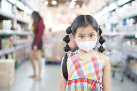Asian child or kid girl wear N95 face mask for close mouth nose and cold cough sick to protect influenza virus  or PM2.5 dust smoke and bacteria for shopping in department store or supermarket