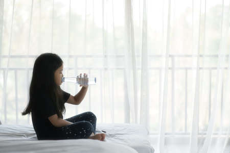 Asian child cute or kid girl wake up and drinking clean water in plastic bottle and bedroom in morning for healthy fresh with thirsty on summer and sit on white bed with curtain at home pre school