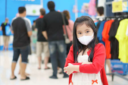 Asian child or kid girl wear white face mask for close mouth nose to flu cough sick for protect PM2.5 dust  virus bacteria to crossed arms on lot of people in department store or shopping mall