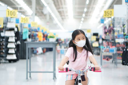 Asian child or kid girl wear face mask with cycling fun or riding bike and shopping bicycle on sport mall in department store to healthy exercise on holiday relax for protect   virus or dust