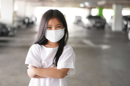 Asian child positive or kid girl smiling wear N95 cloth face mask for close mouth and sick on nose with cold cough and protect PM2.5 dust or influenza virus and bacteria from smoke and crossed arms