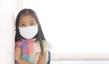 Asian child or kid girl wear N95 cloth face mask for close mouth and sick on nose with cold cough or allergy and protect PM2.5 dust or influenza virus and bacteria from smoke on white space background
