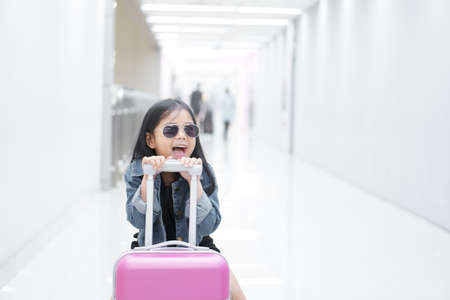 Asian child cute or kid girl smile dragging luggage or baggage and pink suitcase with wear sunglasses and denim shirt or jeans in airport for holiday travel to happy open mouth on summer vacation trip