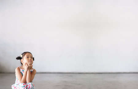 Asian child cute or kid girl thinking sit for new idea and imagination or creative education with vacant smile on street or kindergarten nursery preschool and dirty white wall background with space Stockfoto
