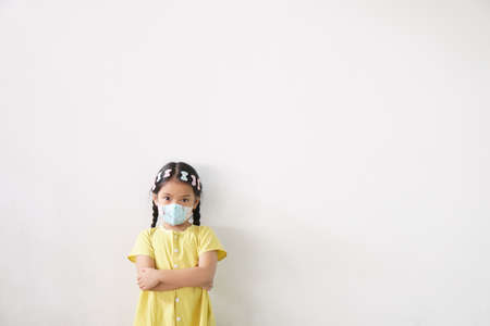 Asian child or kid girl wear N95 paper face mask for close mouth and sick on nose with cold cough and protect PM2.5 dust or influenza virus and bacteria from smoke and arms crossed on white background Stockfoto