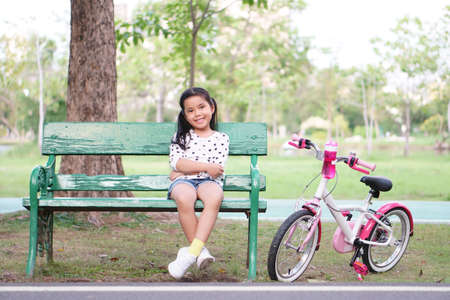 Asian child smile or kid girl sit on wood long chair with pink bicycle for relax and cycling fun with bottle water on bike in public park with green tree garden for sport exercise and healthy biker