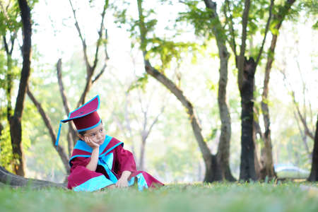 Asian child or kid girl think and little graduate wear gown and degree hat with hand to cheek sit stressed  on nature green graden by kindergarten school success education to congratulation