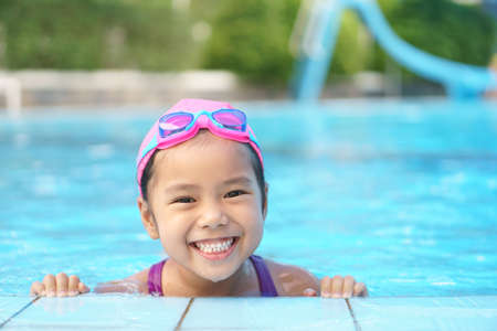 Asian child cute or kid girl wear swimming suit and goggles on swimming pool and smile with happy fun in water park for learn and training swim or refreshing and relax with exercise on summer holiday