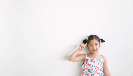 Asian child or kid girl thinking with finger point head and open mouth wow for new idea and imagination or meditation education with smile at nursery school on white wall background and space isolated
