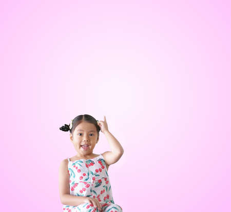Asian child wow or kid girl thinking finger point up on top for new idea to imagination education smiling happy at nursery pre school on pink space background isolated
