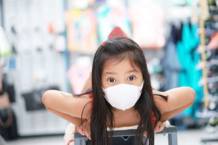 Asian child or kid girl wear white face mask by close mouth nose to flu cough sick for protect PM2.5 dust or coronavirus covid-19 to play enjoy sleep or lie smile in department store or school holiday Stock Photo