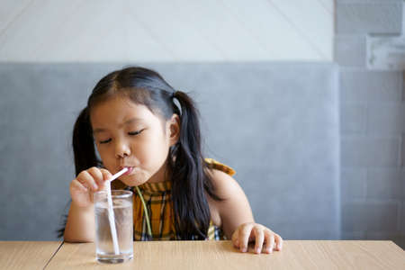 Asian child cute or kid girl drinking cool and clean water by white tube or straw in clear glass cup with ice for fresh and health to thirsty on hot weather summer and table in restaurant with space