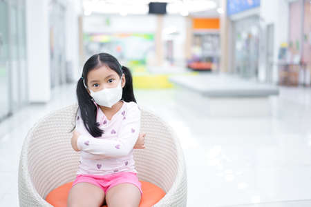 Asian child arms folded or kid girl wearing N95 white face mask to close mouth nose with flu cough sick for protect influenza covid-19 virus or PM2.5 dust on air pollution and sit on chair at school