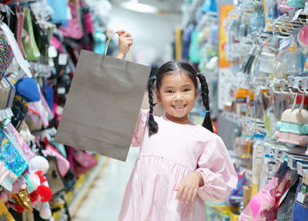 Asian child cute or kid girl smile holding show empty recycle gray paper bag for enjoy shopping and happy fun with save environment at department store or supermarket mall on holiday with pink dress