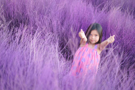 Asian child cute or kid girl lovely smile and make two finger hand mini heart for love valentine day or wedding happy with wearing pink dress on garden meadow or purple grass and violet lavender field Stockfoto
