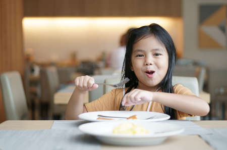 Asian child cute or kid girl smile holding fork to enjoy eating delicious food to hungry on white dish and table with happy for lunch or breakfast and appetizing in morning at restaurant or food court Stockfoto