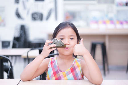 Asian child cute or kid girl enjoy eating rice ball or seaweed roll and thumbs up for japanese food like and appetizing on table and smiling to happy for breakfast or lunch in restaurant or food court