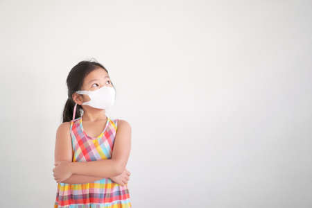 Asian child arms folded or kid girl wearing N95 white face mask for close mouth nose and flu cough sick with protect