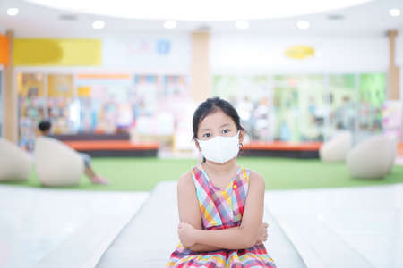 Asian child arms folded or kid girl wearing N95 white face mask to close mouth nose with cold cough sick and sneeze flu for protect influenza
